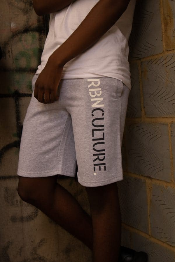 close up view grey urbnculture shorts with text on side of left leg